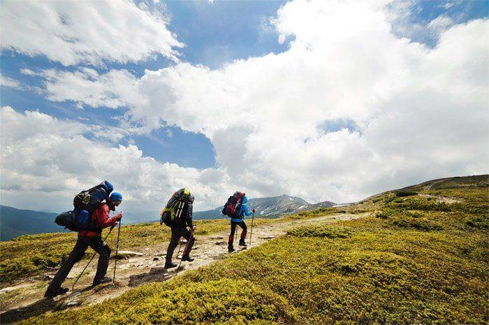 Drei Wanderer in Berglandschaft bei leicht bewölktem Wetter
